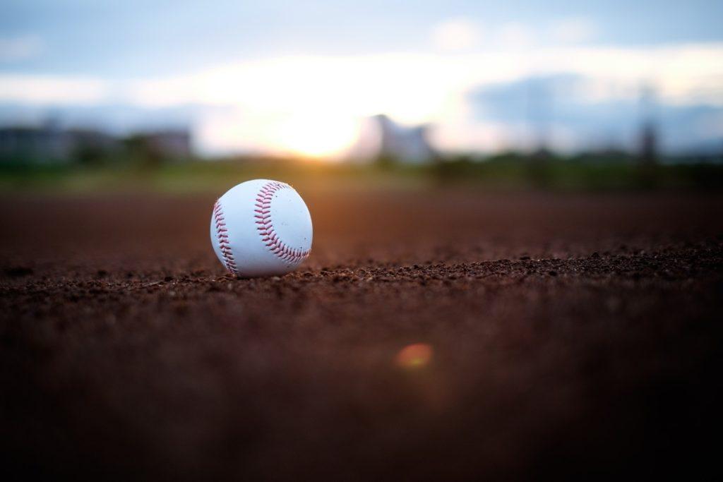 グラウンドに置き去りにされた野球のボールが西日を受けてる様子