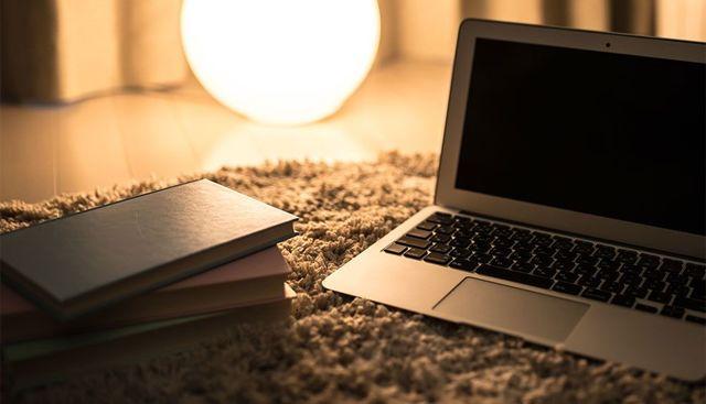 間接照明の明かりに浮かぶノートパソコンと本