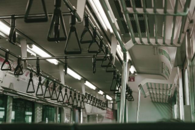 つり革の並んだ走る電車の車内風景