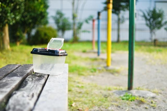 公園のベンチに置かれた虫かご